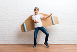 Boy playing with cardboard airplane wings on his back listening to the music and dancing - 230049395