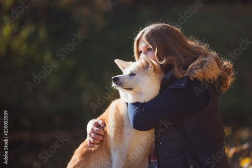 Leinwanddruck Bild Young woman on a walk with her dog breed Akita inu