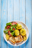 Fried fish with potatoes on wooden table - 230061134