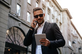 Business. Technology. City walk. Handsome businessman is talking on the mobile phone, using a tablet and smiling while walking outdoors - 230064950