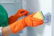 Leinwanddruck Bild - Worker in rubber gloves cleaning empty refrigerator, closeup