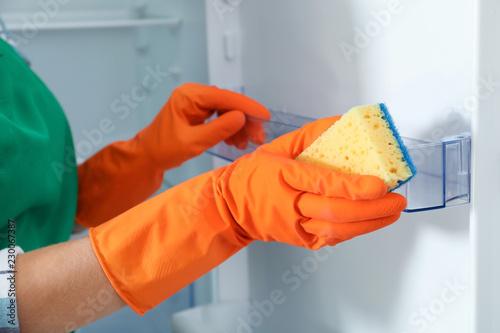 Leinwanddruck Bild Worker in rubber gloves cleaning empty refrigerator, closeup