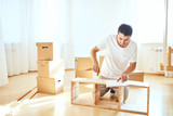 Concentrated young man reading instructions to assemble furniture at home - 230070794