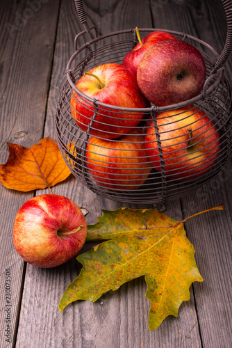 Basket with apples on rustic wooden table - 230073506