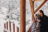 Stylish couple holding hot tea in cups and looking at winter snowy mountains from wooden porch. Happy romantic family with drinks hugging. Space for text. Holiday getaway together. - 230092733