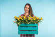 Happy caucasian female florist laughing and holding big box of tulips on blue background