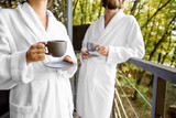Couple in bathrobes with coffee cups outdoors on the balcony in the forest. Cropped image with no face - 230111921
