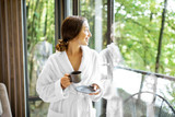 Woman in bathrobe standing near the window with beautiful view on the forest in the modern hotel room - 230112981