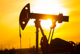 In the evening, the outline. The oil pump, industrial equipment. Field site, oil pumps are running. Rocking machines for oil production in a private sector.