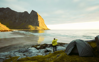 Adventurous man is standing on the beach next to his tent and enjoying the beautiful view during a vibrant sunset. Lofoten  Kvalvika Beach An amazing sunny summer day. Dry grass and heather bushes. © Pavel Kašák