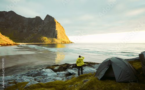 Adventurous man is standing on the beach next to his tent and enjoying the beautiful view during a vibrant sunset. Lofoten Kvalvika Beach An amazing sunny summer day. Dry grass and heather bushes.