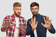 Photo of two guys stretch hands at camera, have displeased expression, feel apathy towards something, ask not bother, dressed in casual clothes, isolated over white background. Negative feeling