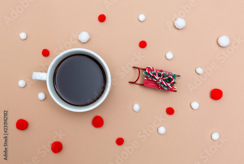 Leinwanddruck Bild Cup of coffee with a miniature snow slide on a light brown paper background
