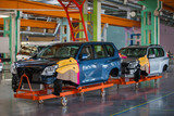 Automotive Plant. Disassembled cars are in a large bright workshop.