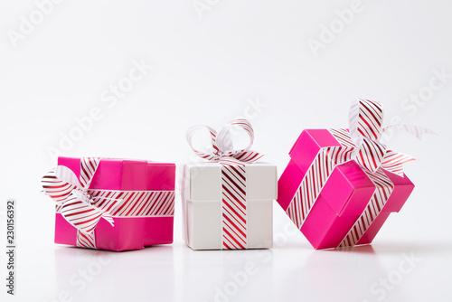 Różowe i białe pudełka z kolorowymi wstążkami na białym tle
