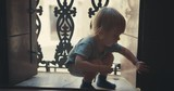 Little toddler playing with the shutters on a balcony - 230182920
