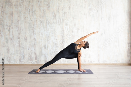 Leinwanddruck Bild Young attractive woman practicing yoga and stretching body.