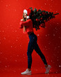 Santa hat Christmas sporting woman holding  xmas tree on her shoulders. Winner energy he red background. it's snowing