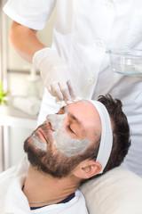 Dłonie kosmetyczki w rękawiczkach zmywają wacikami twarz mężczyzny  © Tomasz