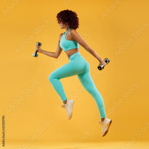 Strong athletic, woman sprinter or runner, running on yellow background with dumbbells wearing sportswear. Fitness and sport motivation. - 230207913