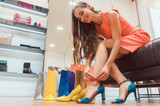 Woman trying to fit new shoes she wants to buy in store