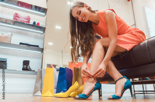 Woman trying to fit new shoes she wants to buy in store © Kzenon