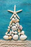 Christmas tree made from sea shells and starfish with sand decoration on wooden blue background, top view, vertical composition - 230218340