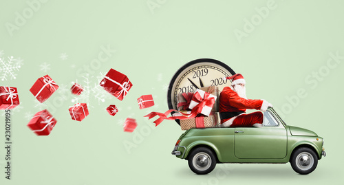 Leinwandbild Motiv Christmas countdown arriving. Santa Claus on car delivering New Year gifts and clock at green background