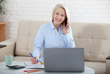 Listening to clients requirements. Beautiful middle aged woman with glasses talking on smart phone and smiling at her working place siting in the office. - 230220713