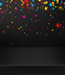 Black festive background with colorful shiny oval confetti.