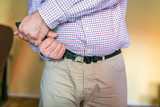 Close Up Of Man Trying Wear His Belt With Tight - 230241324