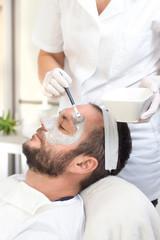 Nakładanie szarej maseczki kosmetycznej na twarz mężczyzny podczas zabiegu kosmetycznego. © Tomasz