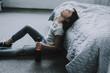 Leinwanddruck Bild - Drunk Sleeping Little Girl Sits on Floor near Bed