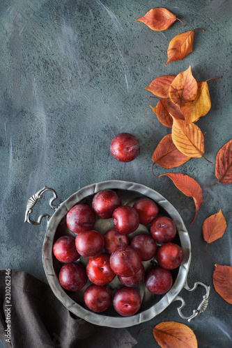 Foto Murales Vintage metal plate with red plums and scattered red and orange Autumn leaves, flat lay with text space