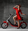 Leinwanddruck Bild - Woman ride sit on motorcycle bicycle scooter pinup retro style laughing smiling red dress