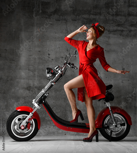 Leinwanddruck Bild Woman ride sit on motorcycle bicycle scooter pinup retro style laughing smiling red dress