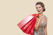 Portrait of happy charming woman holding red shopping bags. Yellow background.