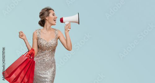 Portret szczęśliwi powabni kobiety mienia czerwieni torba na zakupy. Krzycz w megafon na copyspace. Niebieskie tło.