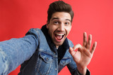 Excited young man in jeans denim jacket take selfie by camera isolated over red background showing okay gesture. - 230283944