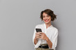 Leinwanddruck Bild - Photo of caucasian woman 20s smiling and holding mobile phone, isolated over gray background
