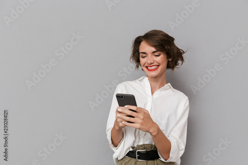 Leinwanddruck Bild Photo of caucasian woman 20s smiling and holding mobile phone, isolated over gray background