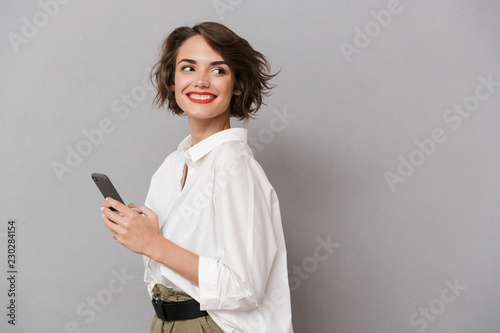 Leinwandbild Motiv Photo of attractive woman 20s smiling and holding mobile phone, isolated over gray background