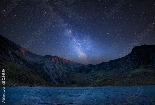 Digital composite Milky Way image of Beautiful landscape image of Llyn Idwal and Devil's Kitchen in Snowdoina