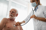 Low angle portrait of shirtless old gentleman looking away with serious expression while doctor checking his breath
