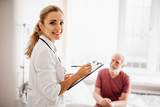 Waist up portrait of smiling lady in white lab coat holding clipboard and pen. Old man sitting on bed on blurred background - 230293947