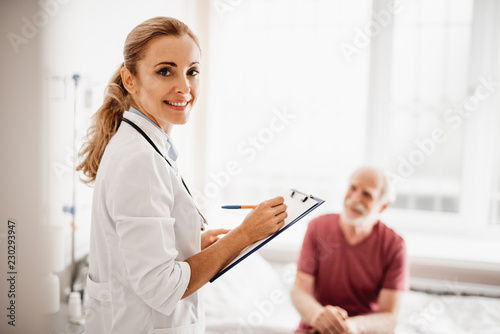 Leinwanddruck Bild Waist up portrait of smiling lady in white lab coat holding clipboard and pen. Old man sitting on bed on blurred background