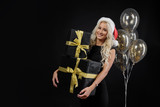 Portrait of beautiful smiling woman in black dress and Santa hat holding stack of gift boxes on the black background. Holding golden balloons and Celebrated a Christmas holiday. Sale concept - 230298919