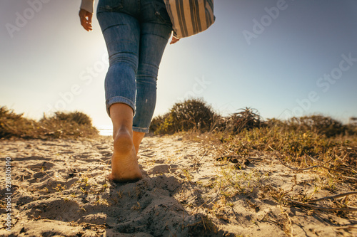 Close up of legs of a woman walking on beach