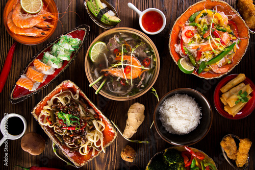 Leinwanddruck Bild Various of asian meals on rustic background , top view , place for text.