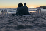 Couple sitting on the beach at sunset - 230307564